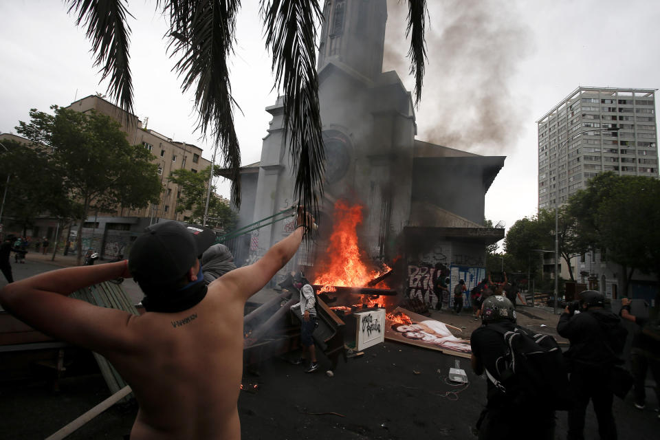 An anti-government protester aims his sling shot at a church after it was looted, in Santiago, Chile, Friday, Nov. 8, 2019. Chile's president on Thursday announced measures to increase security and toughen sanctions for vandalism following three weeks of protests that have left at least 20 dead. (AP Photo/Luis Hidalgo)