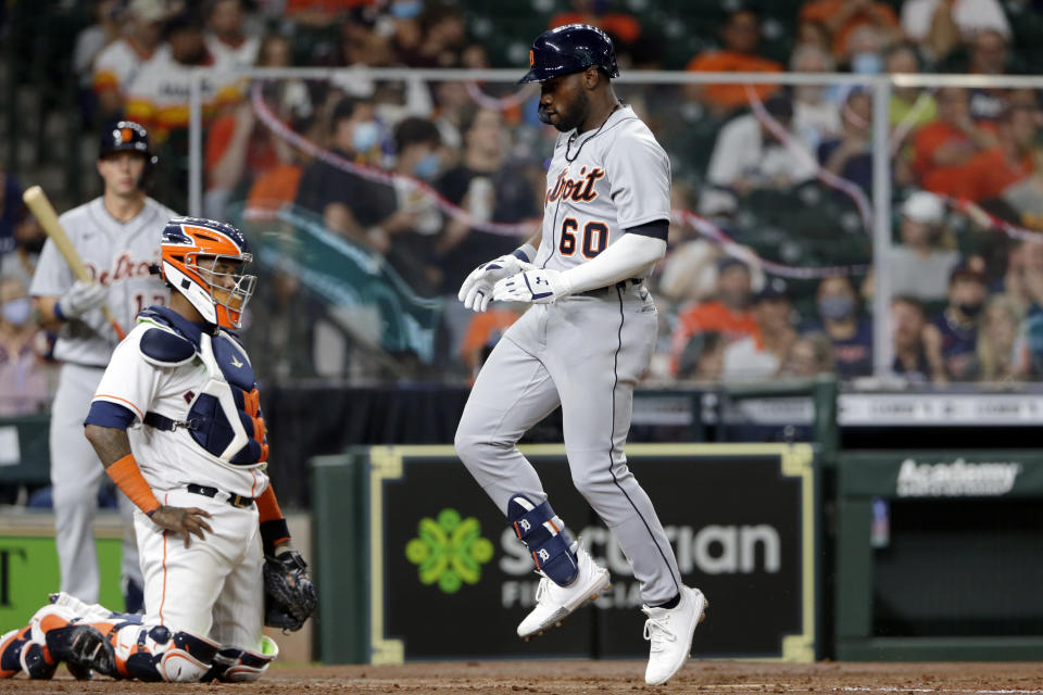 Detroit Tigers' Akil Baddoo (60) reacts as he crosses home plate in front of Houston Astros catcher Martin Maldonado, left, on his home run during the third inning of a baseball game Monday, April 12, 2021, in Houston. (AP Photo/Michael Wyke)