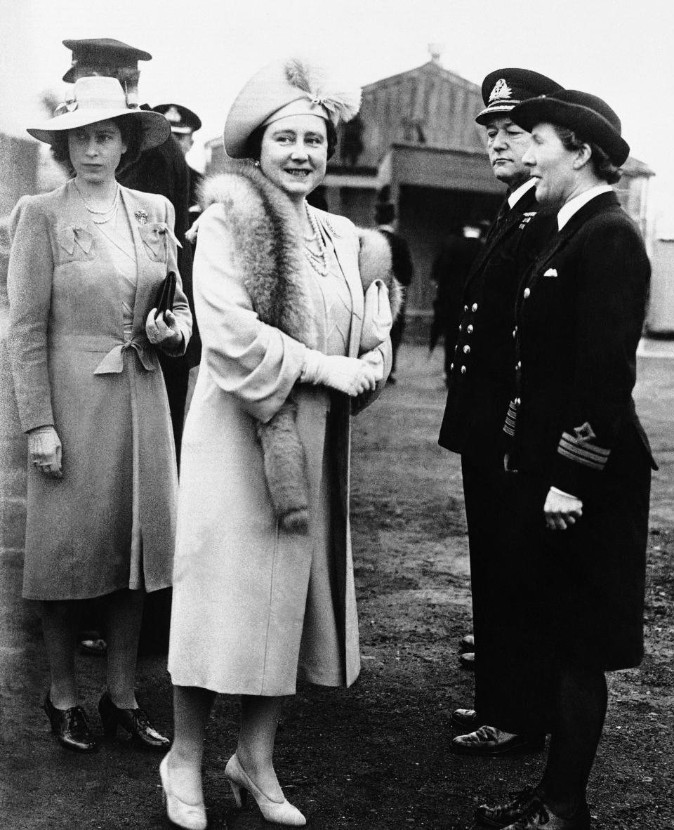 FILE - In this 1945 file photo, Queen Elizabeth and Princess Elizabeth, left, talk to Wren Chief Officer E. King at the shipyards in Belfast during a visit to Northern Ireland when King George opened Ireland's New Parliament. Prince Philip was the longest serving royal consort in British history. In Britain, the husband or wife of the monarch is known as consort, a position that carries immense prestige but has no constitutional role. The wife of King George VI, who outlived him by 50 years, was loved as the Queen Mother. (AP Photo/File)