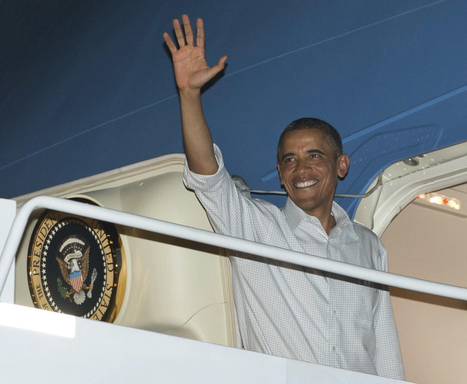 President Barack Obama boards Air Force One at Honolulu Joint Base Pearl Harbor-Hickam, Wednesday, Dec. 26, 2012, in Honolulu, en route to Washington. With a yearend deadline looming before the economy goes off the so called fiscal cliff, the president is cutting short his traditional Christmas holiday in Hawaii. (AP Photo/Carolyn Kaster)