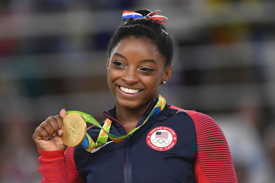 US gymnast Simone Biles celebrates on the podium of the women's floor event final of the Artistic Gymnastics at the Olympic Arena during the Rio 2016 Olympic Games in Rio de Janeiro on August 16, 2016. / AFP / Toshifumi KITAMURA        (Photo credit should read TOSHIFUMI KITAMURA/AFP via Getty Images)