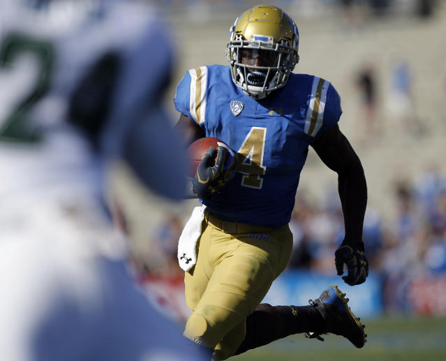 "UCLA running back <a class=""link rapid-noclick-resp"" href=""/ncaaf/players/257298/"" data-ylk=""slk:Bolu Olorunfunmi"">Bolu Olorunfunmi</a> has discovered he can get into the end zone by using defenders as a trampoline. (AP Photo)"