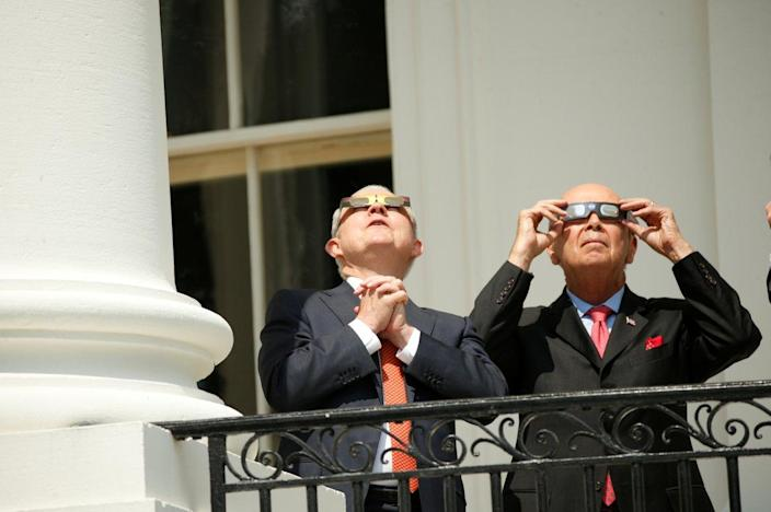 Attorney General Jeff Sessions and Commerce Secretary Wilbur Ross watch the eclipse from the Truman Balcony. (Photo: Kevin Lamarque/Reuters)