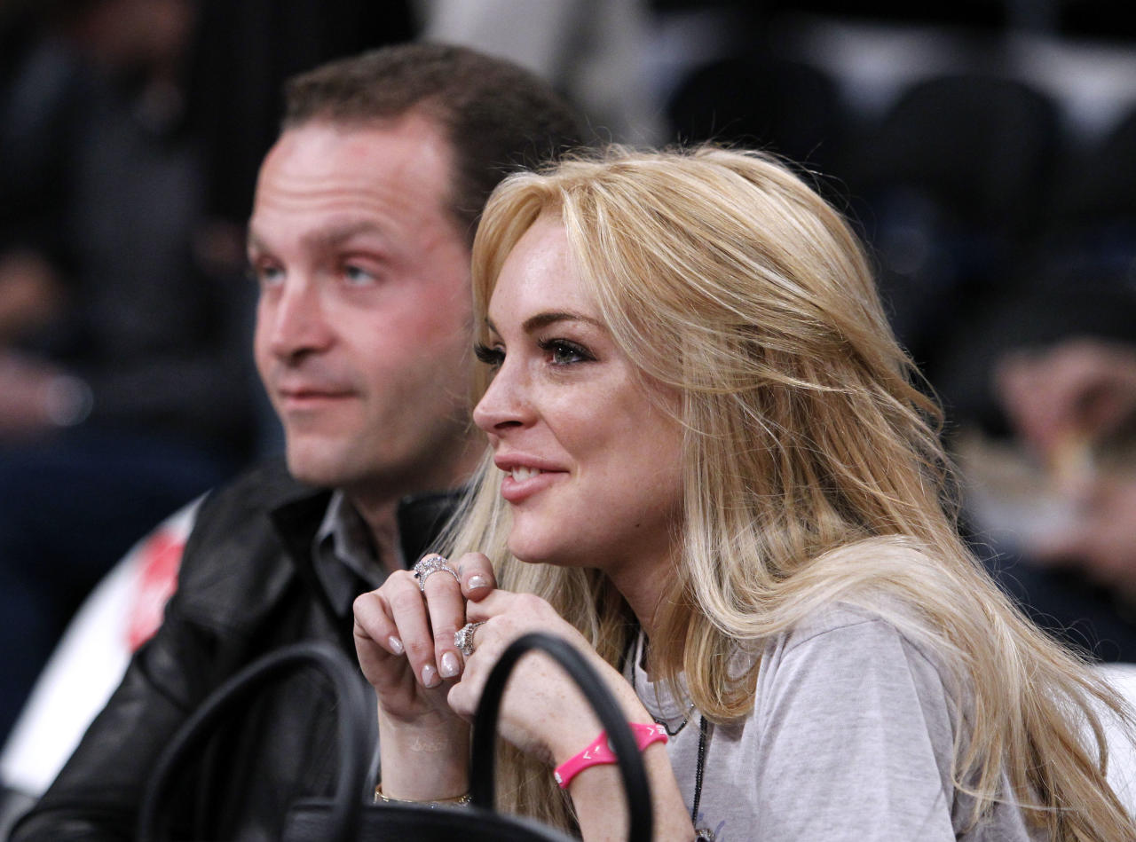 FILE - In this file photo dated Sunday, Jan. 9, 2011, Lndsay Lohan attends the Lakers basketball game courtside with Pascal Mouawad, left, for the game against the New York Knicks, in Los Angeles, USA. Turkey's state-run news agency Anadolu reported Monday Sept. 26, 2016, details of American actress Lindsay Lohan has visiting Syrian refugees at an Istanbul hospital and the home of a refugee family from Aleppo. (AP Photo/Alex Gallardo, FILE)
