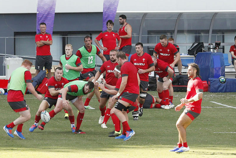 FILE - In this Sept. 16, 2019, file photo, Wales' rugby team players work out in front of the spectators in Kitakyushu, western Japan, ahead of the Rugby World Cup in Japan. Wales assistant coach Rob Howley has been sent home from the Rugby World Cup in Japan over a potential breach of betting rules. (Kyodo News via AP