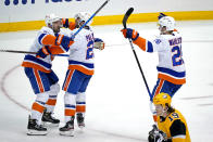 New York Islanders' Kyle Palmieri, center, celebrates with Nick Leddy (2) and Oliver Wahlstrom (26) after putting a shot over Pittsburgh Penguins goaltender Tristan Jarry for the game-winning goal in overtime in Game 1 of an NHL hockey Stanley Cup first-round playoff series in Pittsburgh, Sunday, May 16, 2021. The Islanders won 4-3. (AP Photo/Gene J. Puskar)