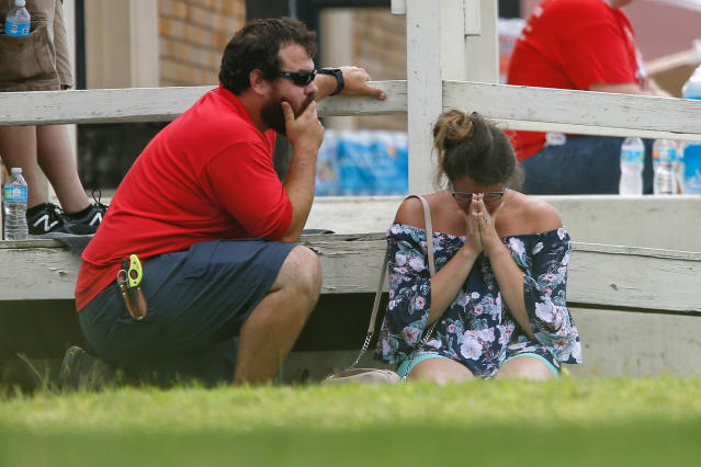 <p>A woman prays in the grass outside the Alamo Gym where parents wait to reunite with their kids following a shooting at Santa Fe High School Friday, May 18, 2018, in Santa Fe, Texas. (Photo: Michael Ciaglo/Houston Chronicle via AP) </p>