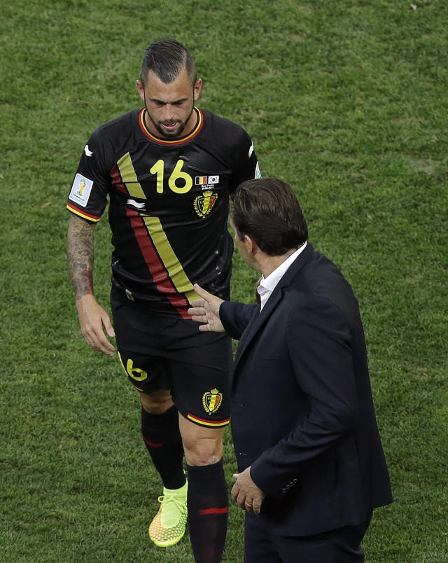 Belgium's Steven Defour (16) walks off the field and is greeted by Belgium's head coach Marc Wilmots after getting a red card during the group H World Cup soccer match between South Korea and Belgium at the Itaquerao Stadium in Sao Paulo, Brazil, Thursday, June 26, 2014. (AP Photo/Andrew Medichini)