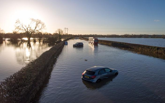 Vehicles remain stranded in the early morning sun by the River Dee