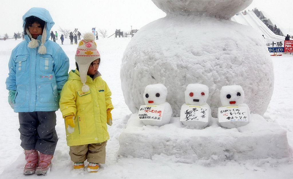 Children stand next to snowmen during the 60th Sapporo Snow Festival in Sapporo, Japan.