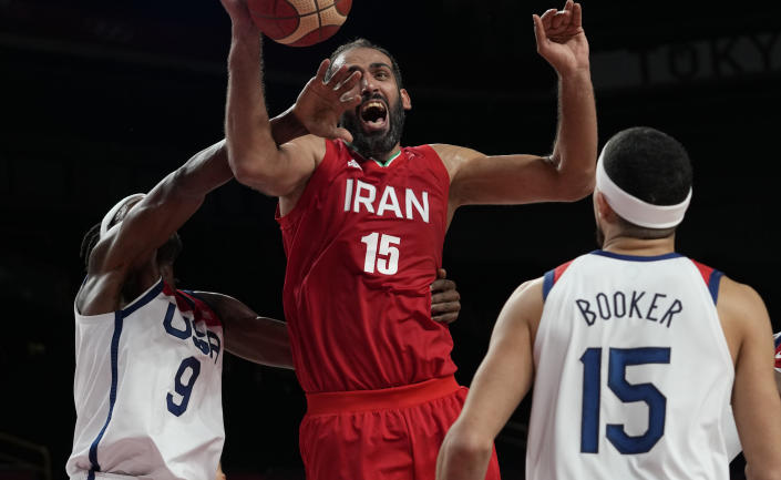 Iran's Hamed Haddadi (15), center, is fouled by United States' Jerami Grant (9), left, during men's basketball preliminary round game at the 2020 Summer Olympics, Wednesday, July 28, 2021, in Saitama, Japan. (AP Photo/Eric Gay)