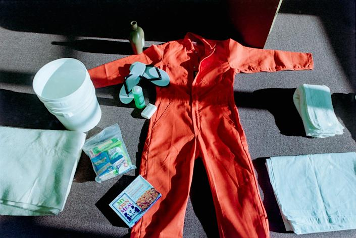 An orange jumpsuit and other items spread out on the floor.