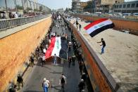 FILE - In this Nov. 8, 2020, file photo, protesters hold Iraqi flags as they head towards Tahrir Square during a demonstration calling for the government to resign, in Baghdad, Iraq. In Iraq, a country that still struggles with the controversial legacy of a U.S.-led invasion in the name of democracy, many people followed the Washington events with a mixture of shock and fascination. (AP Photo/Khalid Mohammed, File)