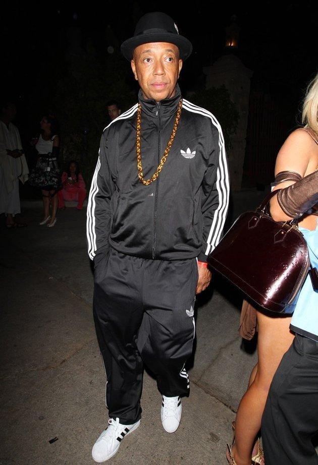 """Russell Simmons took a cue from his younger brother Joseph """"Run"""" Simmons by dressing as one of the guys from Run-D.M.C. The music and fashion mogul wore a track suit, heavy gold chain, and the Adidas sneaks for which the rap group was famous as he hit up the Halloween bash at the Playboy Mansion in L.A. on Saturday. (10/27/2012)"""