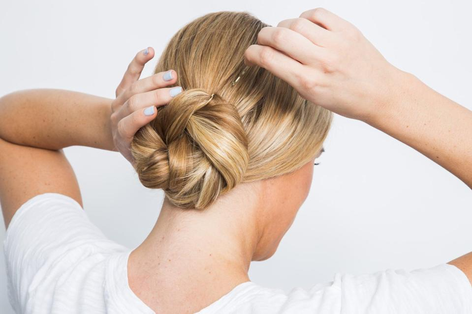 <p>Roll up the twist to form a doughnut shape at the nape of your neck and pin up the twist with bobby pins at the top, bottom, and sides. Then, carefully pull the style to thicken the bun.</p>