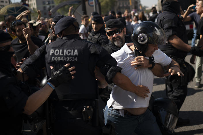 A pro independence demonstrator is blocked by Catalan police officers as he tries to reach a protest of members and supporters of National Police and Guardia Civil demanding better pay in Barcelona, Spain, Saturday, Sept. 29, 2018. (AP Photo/Felipe Dana)