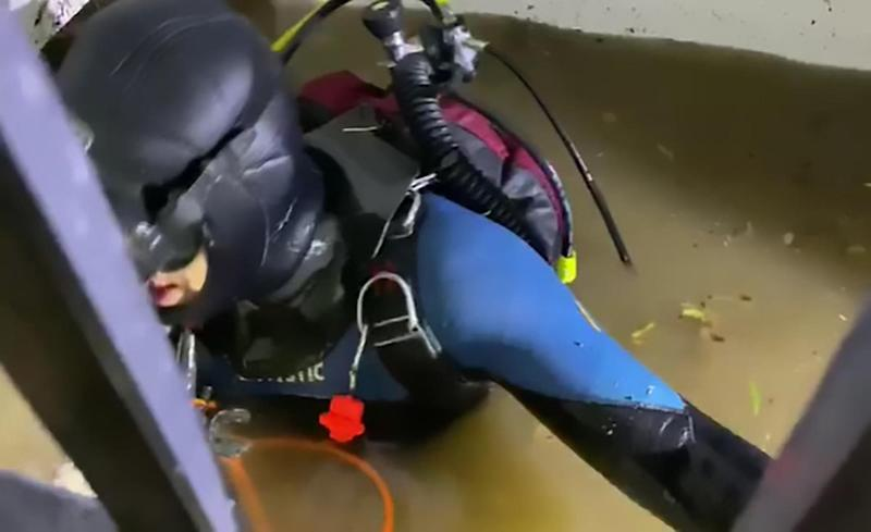 A scuba diver is pictured in a flooded lift shaft.