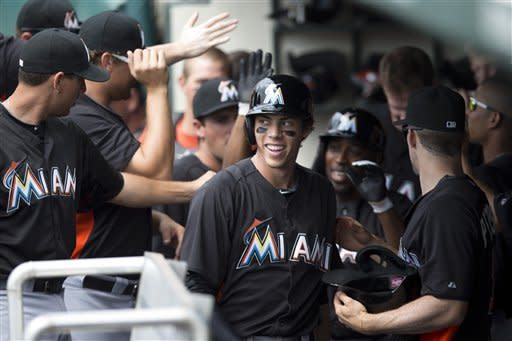 Miami Marlins' Christian Yelich smiles after scoring a run during the first inning of an exhibition spring training baseball game against the Atlanta Braves, Sunday, March 10, 2013, in Kissimmee, Fla. (AP Photo/Evan Vucci)