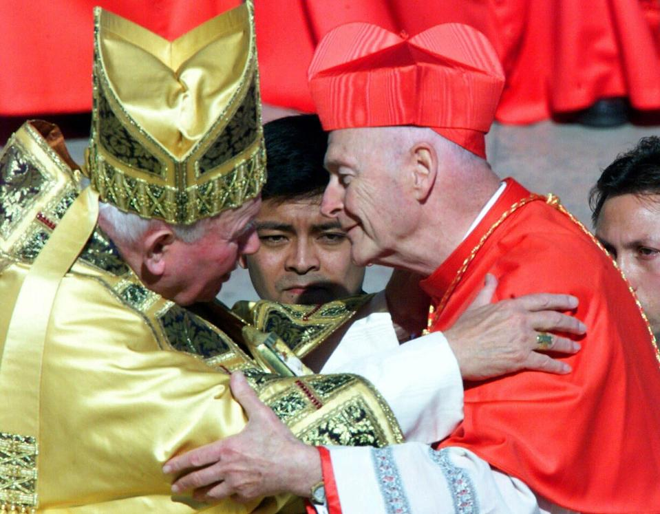 FILE - In this Feb. 21, 2001 file photo, Cardinal Theodore Edgar McCarrick, archbishop of Washington D.C., wearing the three-cornered biretta hat, embraces Pope John Paul II in St. Peter's Square at the Vatican. In a sunlit ceremony of ancient ritual in St. Peter's Square, Pope John Paul II installed a record number of cardinals - 44 new princes of the Roman Catholic Church. (AP Photo/Jerome Delay, File)