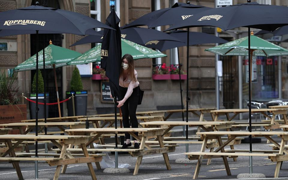 A waitress adjusts a canopy at a restaurant seating area in Glasgow as First Minister Nicola Sturgeon announced the latest coronavirus restrictions to the Scottish Parliament - PA