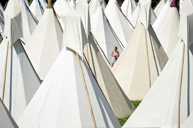 <p>A reveller walks among the tipi tents at the Glastonbury Festival of Music and Performing Arts on Worthy Farm near the village of Pilton in Somerset, South West England, on June 21, 2017. (Photo: Oli Scarff/AFP/Getty Images) </p>