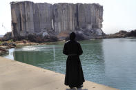 A priest looks towards the towering grain silos, that were gutted in the massive explosion last August, where a Mass will be held to commemorate the first year anniversary of the deadly blast, in Beirut seaport, Lebanon, Wednesday, Aug. 4, 2021. The grim anniversary comes amid an unprecedented economic and financial meltdown and a political stalemate that has kept the country without a functioning government for a full year. (AP Photo/Hussein Malla)