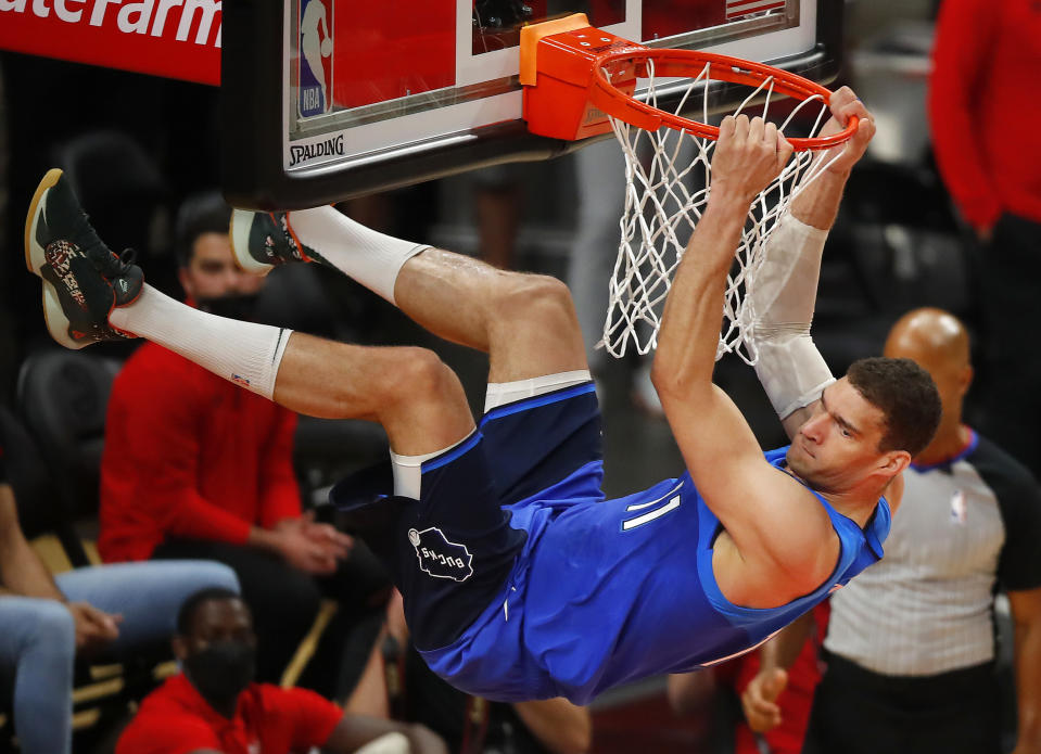 Brook Lopez of the Milwaukee Bucks hangs on the rim after dunking against the Atlanta Hawks. (Photo by Todd Kirkland/Getty Images)