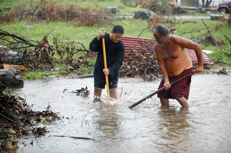 Residents of St. Croix work in floodwaters to clear a drain blocked by debris from Hurricane Maria as the island receives torrential rains on Sept. 30, 2017. (Jonathan Drake / Reuters)