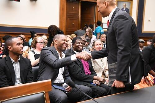 6/19/19 9:00:47 AM -- Washington, DC, U.S.A -- Sen. Cory Booker, D-N.J., greets writer Ta-Nehisi Coates before testifying in front of the House Judiciary Subcommittee on the Constitution, Civil Rights and Civil Liberties during a hearing on reparations for slavery on June 19, 2019 in Washington. The hearing coincides with Juneteenth, a holiday that marks the date that Texas abolished slavery in 1865. -- Photo by Hannah Gaber, USA TODAY Staff ORG XMIT: HG 138097 Reparations Hear 6/19/2019 (Via OlyDrop)