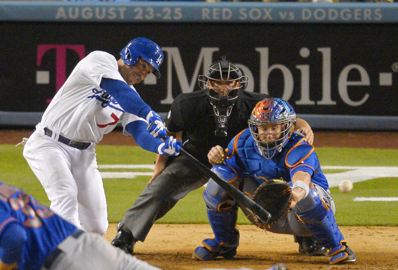Los Angeles Dodgers' Nick Punto, left, hits a two-RBI double as New York Mets catcher John Buck, right, catches and home plate umpire Jeff Kellogg looks on during the fifth inning of their baseball game, Tuesday, Aug. 13, 2013, in Los Angeles. (AP Photo/Mark J. Terrill)