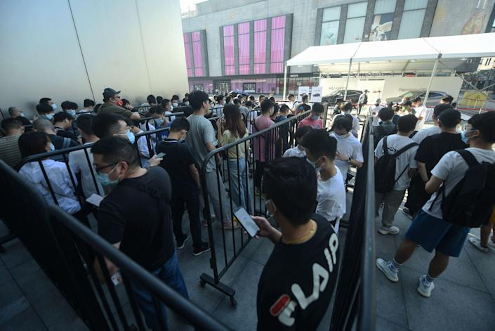 Customers queue to get newly-launched iPhone 13 mobile phones at an Apple store in Hangzhou, in China's eastern Zhejiang province on September 24, 2021.