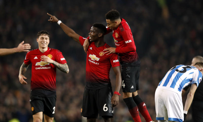 Manchester United's Paul Pogba, center, celebrates scoring against Huddersfield during the English Premier League soccer match at Old Trafford, Manchester, England, Wednesday Dec. 26, 2018. (Martin Rickett/PA via AP)