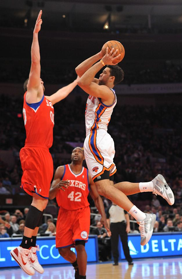 New York Knicks' Landry Fields, right, drives the ball to the basket against Philadelphia 76ers' Spencer Hawes, left, as 76ers' Elton Brand (42) watches during the first half of an NBA basketball game Sunday, Feb. 6, 2011, in New York.