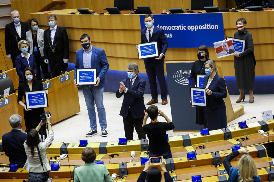 Belarusian opposition politicians are applauded as they hold their prizes during the Sakharov Prize ceremony at the European Parliament in Brussels, Wednesday, Dec. 16, 2020. The European Union has awarded its top human rights prize to the Belarusian democratic opposition. (AP Photo/Francisco Seco)