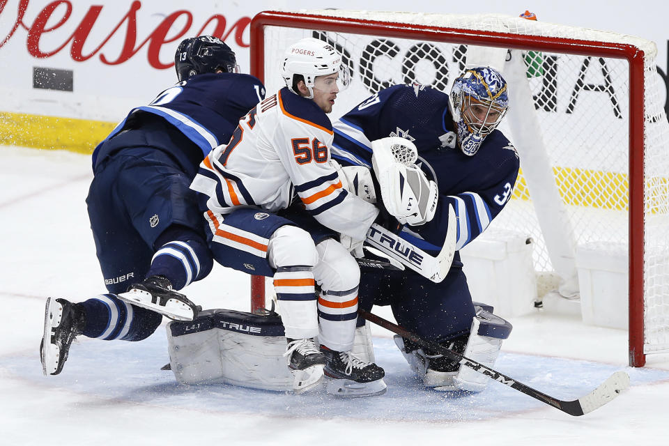 Winnipeg Jets' Pierre-Luc Dubois (13) and Edmonton Oilers' Kailer Yamamoto (56) collide with Jets goaltender Connor Hellebuyck (37) during the third period of an NHL hockey game Wednesday, April 28, 2021, in Winnipeg, Manitoba. (John Woods/The Canadian Press via AP)