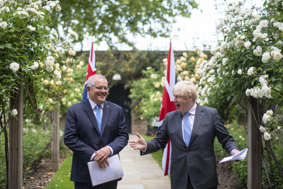 Britain's Prime Minister Boris Johnson, right, walks with Australian Prime Minister Scott Morrison after their meeting, in the garden of 10 Downing Streeet, in London, Tuesday June 15, 2021. Britain and Australia have agreed on a free trade deal that will be released later Tuesday, Australian Trade Minister Dan Tehan said. (Dominic Lipinski/Pool Photo via AP)