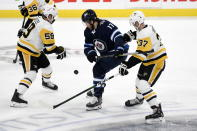 Winnipeg Jets' Adam Lowry (17) battles with Pittsburgh Penguins' Jake Guentzel (59) and Sam Lafferty (37) for the puck during first-period NHL hockey game action in Winnipeg, Manitoba, Sunday, Oct. 13, 2019. (Fred Greenslade/The Canadian Press via AP)