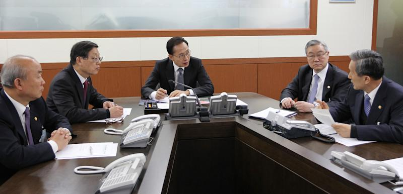 South Korean President Lee Myung-bak, center, talks with Defense Minister Kim Kwan-jin, right, during an emergency meeting of the National Security Council at the presidential house in Seoul, South Korea, Wednesday, Dec. 12, 2012. North Korea fired a long-range rocket Wednesday in its second launch under its new leader, South Korean officials said, defying warnings from the U.N. and Washington only days before South Korean presidential elections.(AP Photo/Yonhap) KOREA OUT