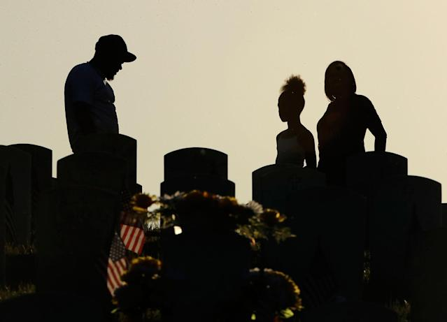 <p>Visitors pause at a grave at Leavenworth National Cemetery on May 28, 2017, in Leavenworth, Kan. (Photo: Charlie Riedel/AP) </p>