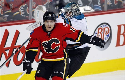 San Jose Sharks goalie Antti Niemi, rear, of Finland, loses his balance after getting bumped by Calgary Flames' Michael Cammalleri during the first period of an NHL hockey game, Sunday, Jan. 20, 2013, in Calgary, Alberta. (AP Photo/The Canadian Press, Jeff McIntosh)