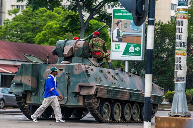 A man walks past an armored personnel carrier stationed at an intersection in Harare as Zimbabwean soldiers regulate traffic on Nov. 15, 2017. (- via Getty Images)