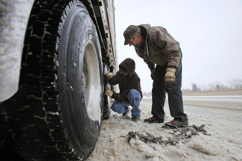 Truck drivers Kevin Kropf, 32, of Montrose, Colo., left, and Edwin Hostetler, of Hotchkiss, Colo., prepare a cattle truck with chins before heading up I-70 as a snow storm hits the Denver metro area Friday, Feb. 3, 2012 in Denver. A powerful winter storm swept across Colorado on Friday as it headed east, bringing blizzard warnings to eastern Colorado and winter storm warnings for southeast Wyoming, western Kansas and western Nebraska. The storm stretched as far south as New Mexico, where Department of Transportation reported difficult driving conditions on several state highways because of the winter weather, leaving highways snow packed and icy. (AP Photo/Barry Gutierrez)