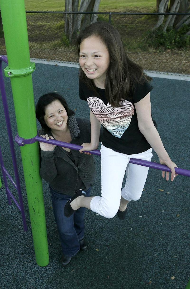 Joyce Chen and her daughter Kathryn, 10, pose for photographs in San Francisco, Wednesday, May 29, 2013. A new poll finds that one in five unmarried women would consider having a child on their own, and more than a third would consider adopting solo, just one indication of America's changing family structures. (AP Photo/Jeff Chiu)