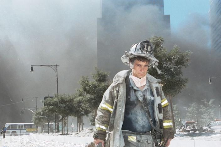 """An unidentified New York City fireman walks away from Ground Zero after the collapse of the towers. Photographer Anthony Correia told LIFE.com of this picture: """"He just looked so exhausted, so beat up."""" Correia knelt down and took his shot as the man walked by. """"I acknowledged him, and he acknowledged me. But he never stopped."""" The steady gaze, meanwhile, of this lone firefighter allows us a window into the experience of literally thousands of rescue workers and first responders. I was in there, his eyes seem to say. Be thankful that you can't imagine what I saw. <br><br>(Photo: Anthony Correia/Getty Images)<br><br>For the full photo collection, go to <a href=""""http://www.life.com/gallery/59971/911-the-25-most-powerful-photos#index/0"""" rel=""""nofollow noopener"""" target=""""_blank"""" data-ylk=""""slk:LIFE.com"""" class=""""link rapid-noclick-resp"""">LIFE.com</a>"""