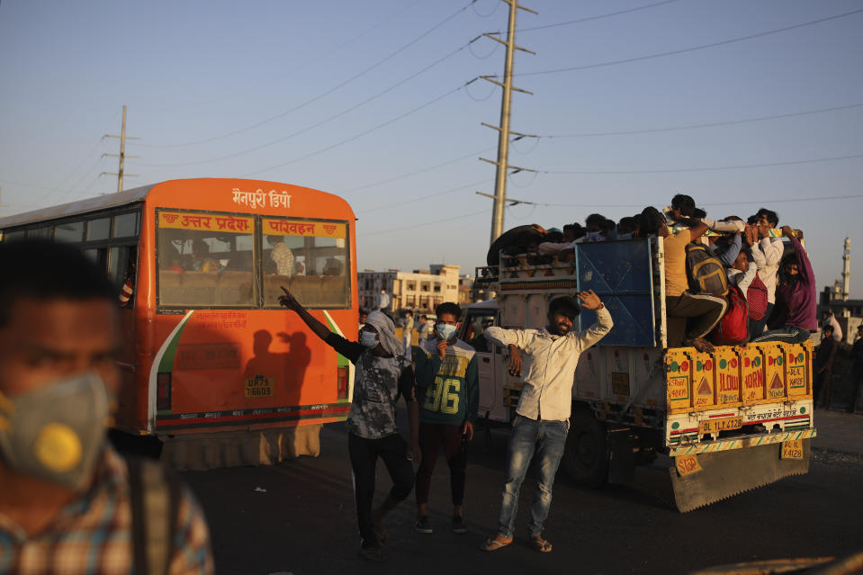 Indian men try to stop vehicles for migrant workers waiting for transportation to their respective villages following a lockdown amid concern over spread of coronavirus in New Delhi, India, Saturday, March 28, 2020. Authorities sent a fleet of buses to the outskirts of India's capital on Saturday to meet an exodus of migrant workers desperately trying to reach their home villages during the world's largest coronavirus lockdown. Thousands of people, mostly young male day laborers but also families, fled their New Delhi homes after Prime Minister Narendra Modi announced a 21-day lockdown that began on Wednesday and effectively put millions of Indians who live off daily earnings out of work. (AP Photo/Altaf Qadri)