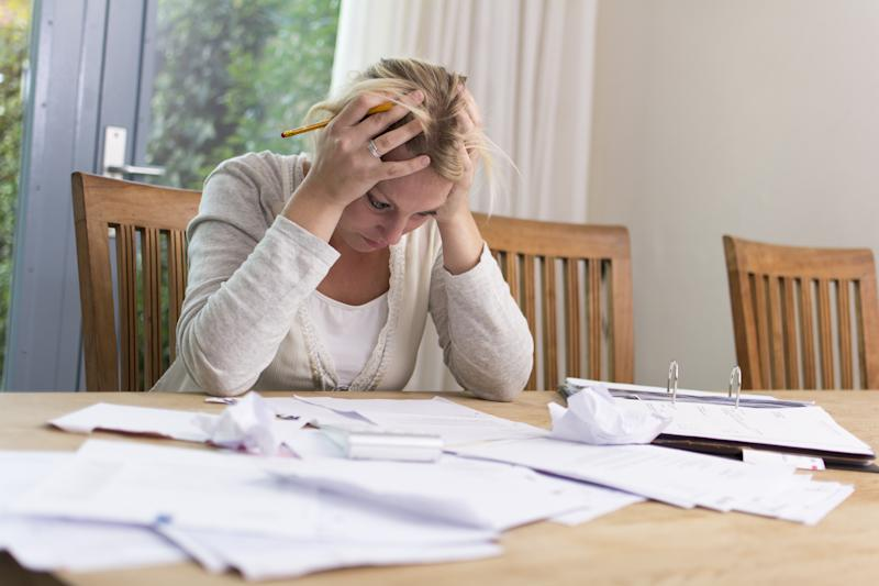 Woman looking at papers spread out on table, holding her head