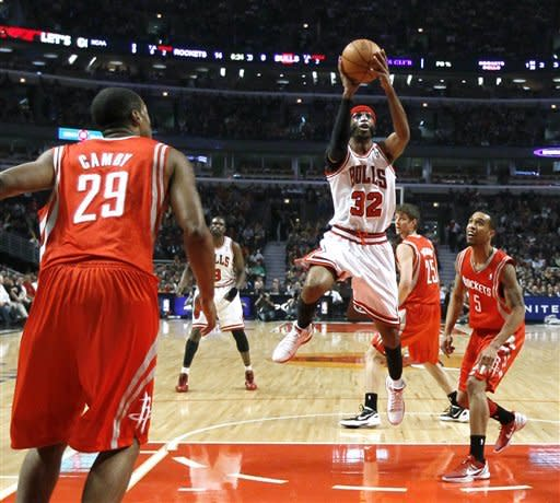 Chicago Bulls guard Richard Hamilton (32) shoots between Houston Rockets center Marcus Camby (29) and guard Courtney Lee during the first half of an NBA basketball game Monday, April 2, 2012, in Chicago. (AP Photo/Charles Rex Arbogast)