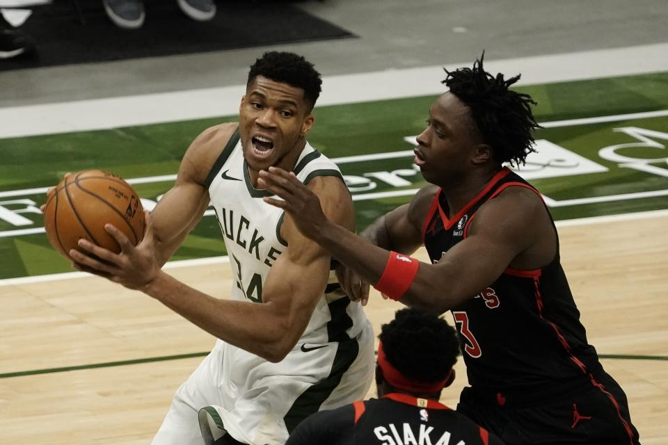 Giannis Antetokounmpo with the ball in both of his hands as OG Anunoby defends.