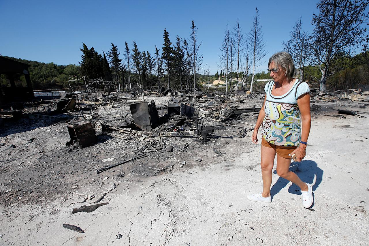<p>A woman walks past charred debris of vehicles that were destroyed by fire in a parking lot for camping cars in Bormes-les-Mimosas, in the Var department, France, July 26, 2017, after firefighters evacuated thousands of campers and local residents when a wildfire broke out on France's tourist-thronged Riviera coast overnight. (Jean-Paul Pelissier/Reuters) </p>
