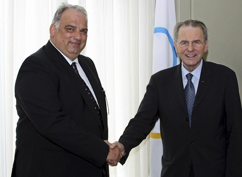 In this image made available by FILA News Bureau, International Olympic Committee President Jacques Rogge, right, shakes hands with the acting head of wrestling's world governing body Nenad Lalovic at the IOC headquarters in in Lausanne Switzerland Thursday March 7, 2013. Lolovic met with IOC President Jacques Rogge and promised the sport would work hard in its fight to retain Olympic status. (AP Photo/FILA News Bureau)